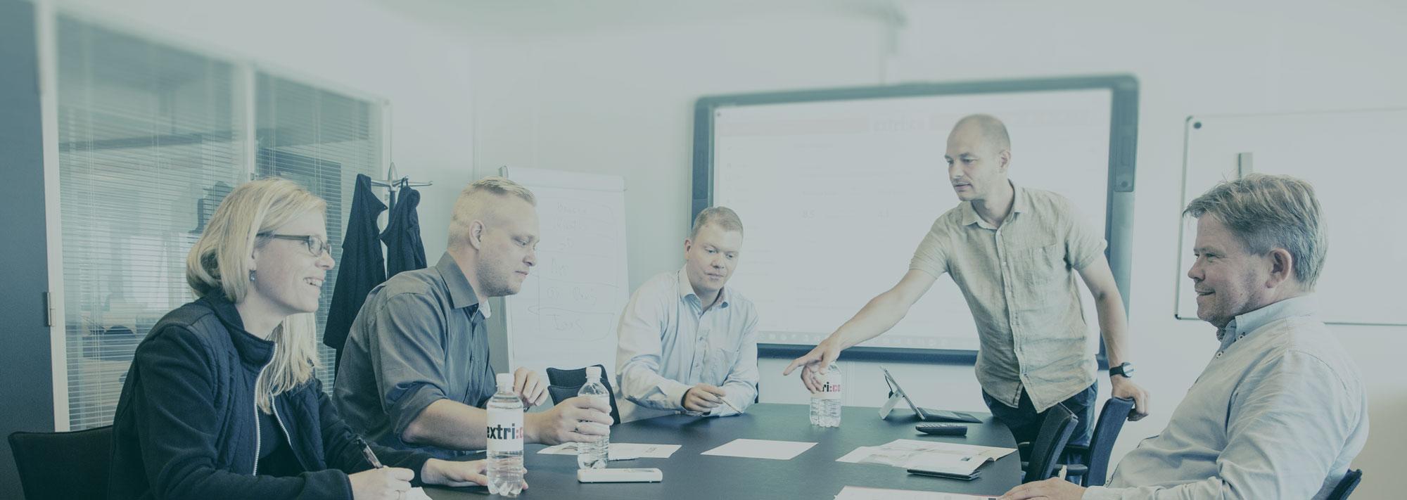 medarbejdere-gennemgår-projekt-i-mødelokale